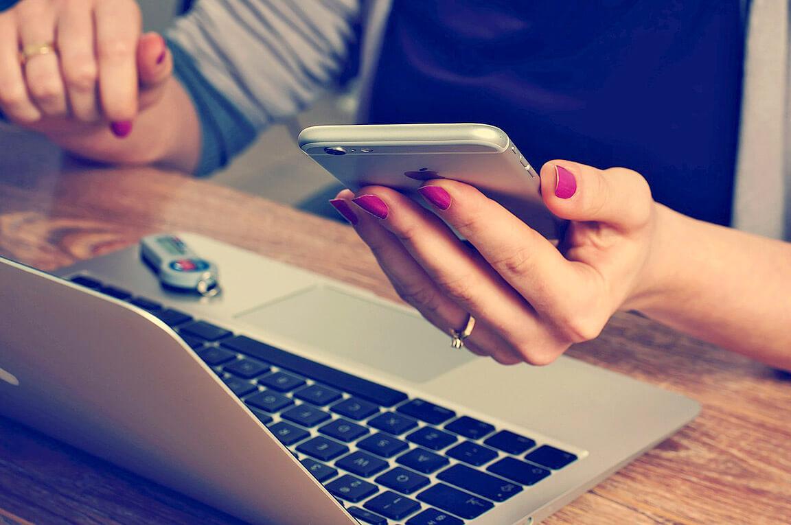 knowy young people, Frau mit smartphone sitzend liest sich KNOWY Website durch