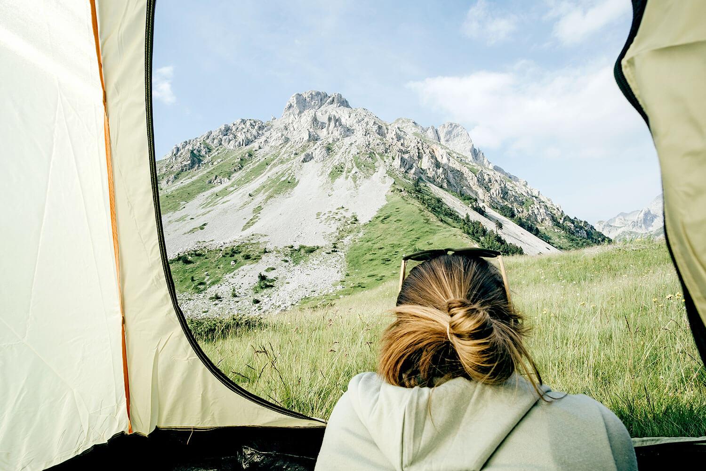 knowy young people- junge Frau schaut auf den Berg, liegend im Zelt